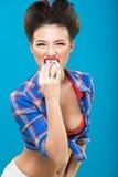 Νέο κορίτσι με το στηθόδεσμο στην καρφίτσα επάνω στο ύφος που τρώει ένα κέικ Στοκ Εικόνες