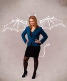 Νέο κορίτσι με το σχεδιασμό κέρατων και φτερών διαβόλων Στοκ Φωτογραφίες