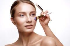 Νέο κορίτσι με το τέλειο λάμποντας δέρμα και το nude makeup Ένα όμορφο πρότυπο με ένα ίδρυμα και τις βούρτσες για τις καλλυντικές Στοκ εικόνα με δικαίωμα ελεύθερης χρήσης