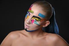 Νέο κορίτσι με το φωτεινό γεωμετρικό σχέδιο στο πρόσωπό της ο σκοτεινός δαίμονας αποκριές ανασκόπησης κάνει το αρσενικό ύφος πορτ Στοκ εικόνα με δικαίωμα ελεύθερης χρήσης