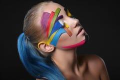 Νέο κορίτσι με το φωτεινό γεωμετρικό σχέδιο στο πρόσωπό της ο σκοτεινός δαίμονας αποκριές ανασκόπησης κάνει το αρσενικό ύφος πορτ Στοκ Εικόνα
