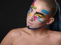 Νέο κορίτσι με το φωτεινό γεωμετρικό σχέδιο στο πρόσωπό της ο σκοτεινός δαίμονας αποκριές ανασκόπησης κάνει το αρσενικό ύφος πορτ Στοκ φωτογραφία με δικαίωμα ελεύθερης χρήσης