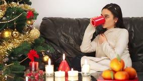 Νέο κορίτσι με το φλυτζάνι του τσαγιού κοντά στο χριστουγεννιάτικο δέντρο απόθεμα βίντεο
