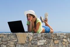 Νέο κορίτσι με το lap-top, στα σορτς και το άσπρο καπέλο Στοκ Φωτογραφίες
