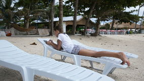 Νέο κορίτσι με το PC ταμπλετών στην παραλία φιλμ μικρού μήκους