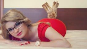 Νέο κορίτσι με eyeglasses στο κρεβάτι στοκ εικόνα με δικαίωμα ελεύθερης χρήσης