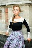 Νέο κορίτσι μόδας που αναρωτιέται στο τουβλότοιχο στοκ φωτογραφία