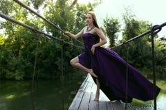 Νέο κορίτσι ομορφιάς στο κυματίζοντας ιώδες φόρεμα που στέκεται μόνο Στοκ Φωτογραφία