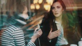 Νέο κορίτσι πίσω από το γυαλί καφέδων που μιλά στο smartphone εκμετάλλευσης φίλων υπό εξέταση απόθεμα βίντεο