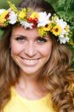 Νέο κορίτσι πορτρέτου στο κίτρινο φόρεμα με το στεφάνι λουλουδιών για το κεφάλι Περπατώντας στο πάρκο, θερμή θερινή ημέρα στοκ εικόνα