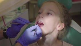 Νέο κορίτσι που έχει τα δόντια της καθορισμένων στον οδοντίατρο ` s Καθαρισμός τερηδόνων Ο οδοντίατρος βουρτσίζει τα δόντια του μ απόθεμα βίντεο