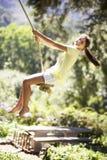 Νέο κορίτσι που έχει τη διασκέδαση στην ταλάντευση σχοινιών Στοκ Φωτογραφία