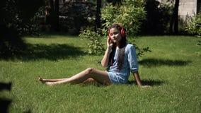 Νέο κορίτσι που ακούει τη μουσική στα ακουστικά που χρησιμοποιούν τη συνεδρίαση smartphone στη χλόη στο πάρκο στον ηλιόλουστο και φιλμ μικρού μήκους