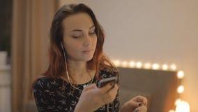 Νέο κορίτσι που ακούει τη μουσική στο τηλέφωνό σας μέσω app απόθεμα βίντεο