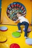 Νέο κορίτσι που αναρριχείται επάνω στην κεκλιμένη ράμπα στη σήραγγα στο μαλακό κέντρο παιχνιδιού Στοκ φωτογραφία με δικαίωμα ελεύθερης χρήσης
