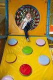 Νέο κορίτσι που αναρριχείται κάτω από την κεκλιμένη ράμπα στο μαλακό κέντρο παιχνιδιού Στοκ Εικόνες