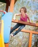 Νέο κορίτσι που αναρριχείται στην παιδική χαρά των παιδιών Στοκ Φωτογραφίες