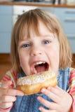 Νέο κορίτσι που απολαμβάνει ζαχαρούχο Doughnut στοκ φωτογραφίες