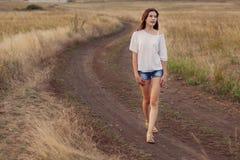Νέο κορίτσι που απολαμβάνει υπαίθρια τη φύση Αυτή που περπατά κατά μήκος του δρόμου Στοκ Φωτογραφία
