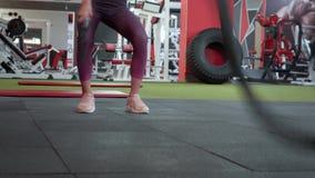 Νέο κορίτσι που ασκεί σκληρά με το σχοινί μάχης κατά τη διάρκεια της διαγώνιας περιόδου άσκησης Το όμορφο κορίτσι στην αθλητική λ απόθεμα βίντεο