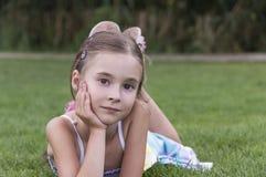 Νέο κορίτσι που βάζει και που θέτει στη χλόη στοκ φωτογραφίες