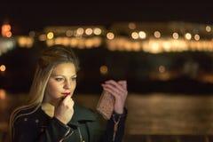 Νέο κορίτσι που βάζει το κόκκινο κραγιόν που εξετάζει Smartphone, νύχτα lig Στοκ Φωτογραφία