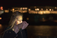 Νέο κορίτσι που βάζει το κόκκινο κραγιόν που εξετάζει Smartphone, νύχτα lig Στοκ Εικόνα