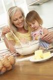 Νέο κορίτσι που βοηθά τη γιαγιά για να ψήσει τα κέικ στην κουζίνα Στοκ φωτογραφία με δικαίωμα ελεύθερης χρήσης
