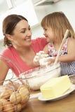 Νέο κορίτσι που βοηθά τη μητέρα για να ψήσει τα κέικ στην κουζίνα Στοκ Φωτογραφίες