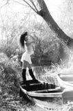 Νέο κορίτσι που βρίσκεται σε μια βάρκα που επιπλέει στη λίμνη Στοκ Εικόνα