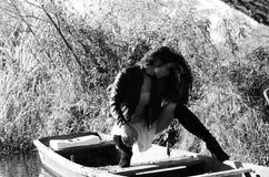 Νέο κορίτσι που βρίσκεται σε μια βάρκα που επιπλέει στη λίμνη Στοκ φωτογραφία με δικαίωμα ελεύθερης χρήσης