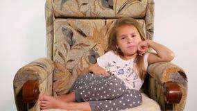 Νέο κορίτσι που βρίσκεται στην πολυθρόνα με μακρινό και που ψάχνει έναν ενδιαφέροντα κινηματογράφο φιλμ μικρού μήκους