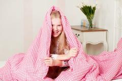 Νέο κορίτσι που βρίσκεται στο κρεβάτι κάτω από τις καλύψεις Στοκ Φωτογραφίες