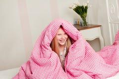 Νέο κορίτσι που βρίσκεται στο κρεβάτι κάτω από τις καλύψεις Στοκ φωτογραφίες με δικαίωμα ελεύθερης χρήσης