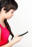 Νέο κορίτσι που γράφει ή που διαβάζει sms Στοκ φωτογραφία με δικαίωμα ελεύθερης χρήσης