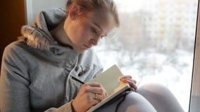 Νέο κορίτσι που γράφει στο περιοδικό της καθμένος σε ένα μεγάλο παράθυρο. φιλμ μικρού μήκους
