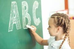 Νέο κορίτσι που γράφει ABC στον πράσινο πίνακα κιμωλίας Στοκ Φωτογραφίες