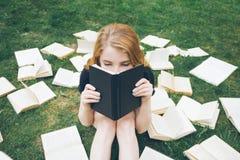 Νέο κορίτσι που διαβάζει ένα βιβλίο στη χλόη Ένα κορίτσι μεταξύ των βιβλίων στο θερινό κήπο στοκ φωτογραφίες