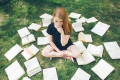 Νέο κορίτσι που διαβάζει ένα βιβλίο στη χλόη Ένα κορίτσι μεταξύ των βιβλίων στο θερινό κήπο στοκ εικόνες με δικαίωμα ελεύθερης χρήσης