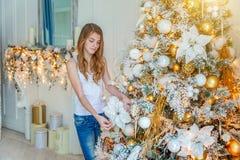 Νέο κορίτσι που διακοσμεί το χριστουγεννιάτικο δέντρο στο σπίτι στοκ εικόνες με δικαίωμα ελεύθερης χρήσης