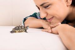 Νέο κορίτσι που εξετάζει μια μικρή χελώνα Στοκ Φωτογραφίες