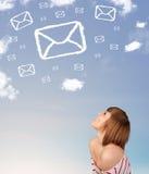 Νέο κορίτσι που εξετάζει τα σύννεφα συμβόλων ταχυδρομείου στο μπλε ουρανό Στοκ Εικόνες