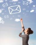 Νέο κορίτσι που εξετάζει τα σύννεφα συμβόλων ταχυδρομείου στο μπλε ουρανό Στοκ Φωτογραφία
