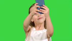 Νέο κορίτσι που εξετάζει τη λήψη χαμόγελου καμερών selfie σε μια πράσινη οθόνη, κλειδί χρώματος απόθεμα βίντεο