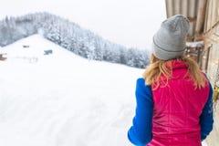Νέο κορίτσι που εξετάζει το χιονώδες εξοχικό σπίτι θερέτρου εξοχικών σπιτιών χειμερινών δασικό χωριών ξύλινο Στοκ Φωτογραφία