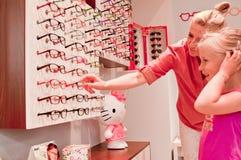 Νέο κορίτσι που επιλέγει τα γυαλιά Στοκ Εικόνες
