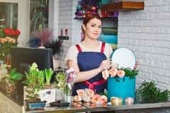 Νέο κορίτσι που εργάζεται σε ένα ανθοπωλείο Στοκ Εικόνες