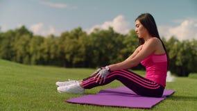 Νέο κορίτσι που θερμαίνει πριν από την περίοδο άσκησης στο πάρκο μπροστινή γυναίκα τεντώματος χεριών ο εστίασης προσώπου δ φ έξω  απόθεμα βίντεο