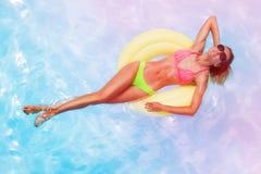 Νέο κορίτσι που κάνει ηλιοθεραπεία στο δαχτυλίδι στην πισίνα στοκ φωτογραφία