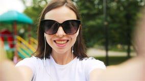 Νέο κορίτσι που κάνει τηλεοπτικό selfie και που έχει τη διασκέδαση στο πάρκο φιλμ μικρού μήκους